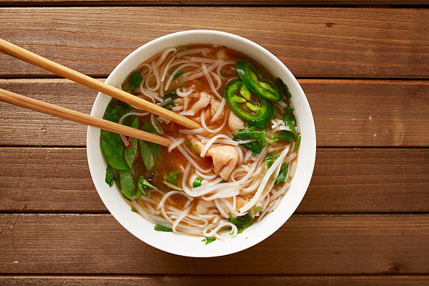 eating a bowl of vietnamese beef pho eating a bowl of vietnamese beef pho with chopsticks shot top down rice noodles stock pictures, royalty-free photos & images