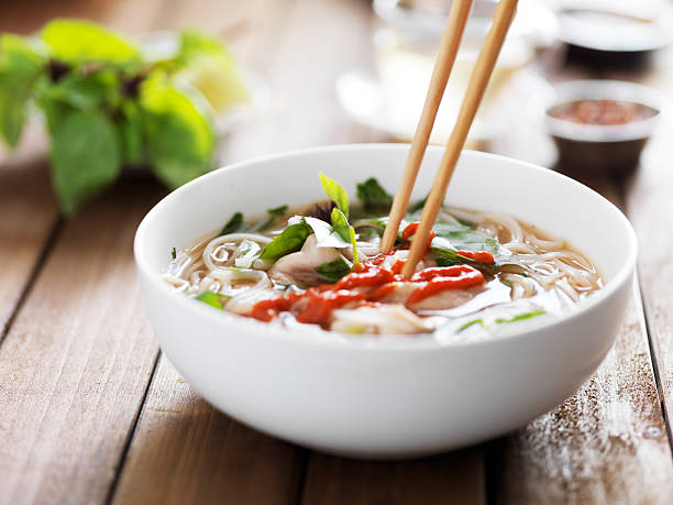 eating a bowl of vietnamese beef pho with chopsticks eating a bowl of vietnamese beef pho with chopsticks and spicy sriracha sauce rice noodles stock pictures, royalty-free photos & images