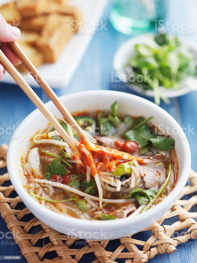 eating a bowl of vietnamese Pho Tai beef soup stock photo