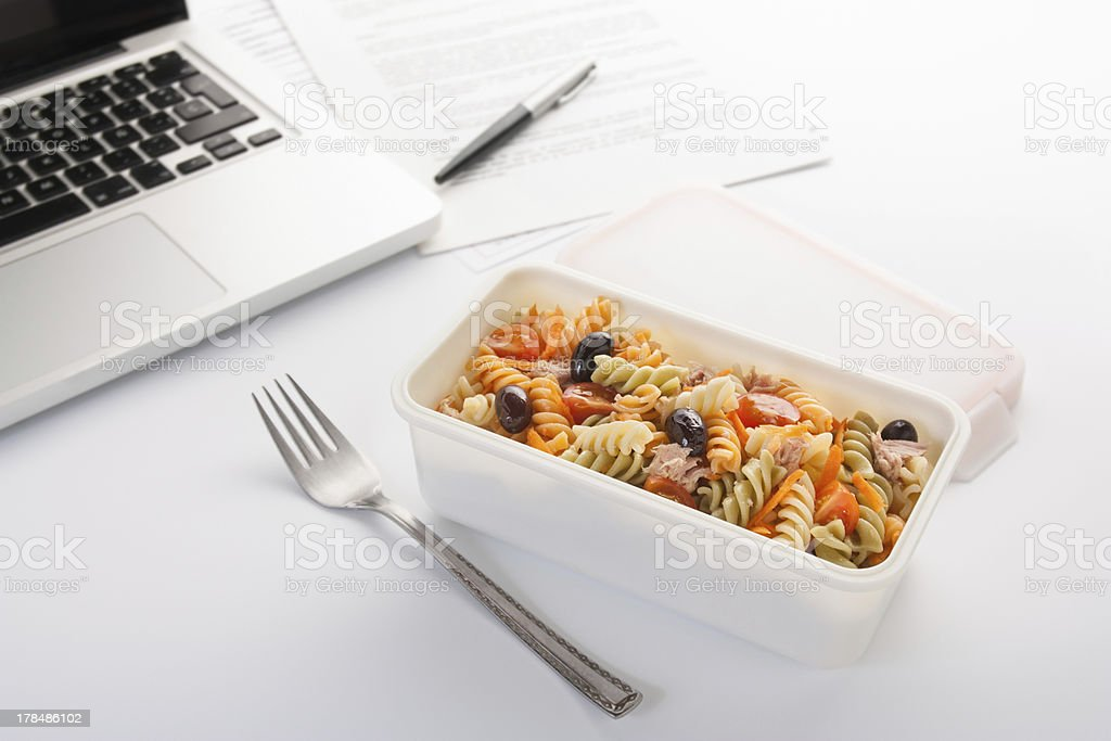 Eating a pasta salad in the office stock photo