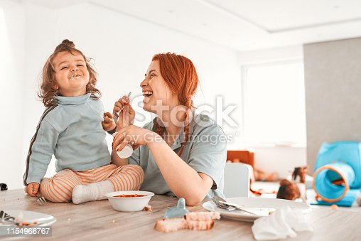 lifestyle shot, mother with her little girl eating and smiling.