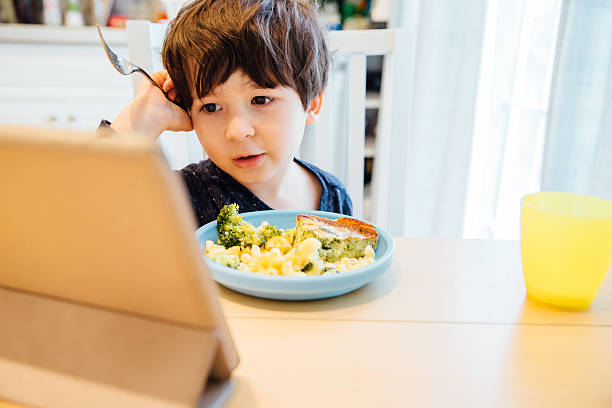 Eating and Watching a Tablet Computer stock photo