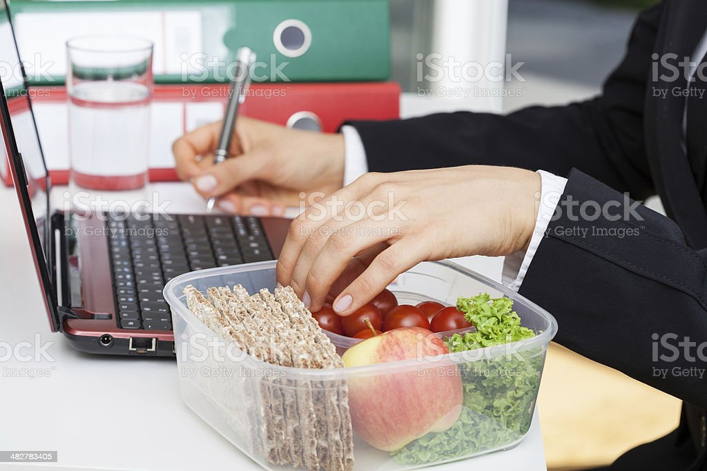 Eating and working stock photo