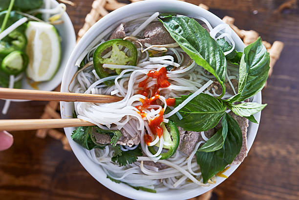 eating beef pho with spicy sriracha sauce shot top down - pho soup stock photos and pictures