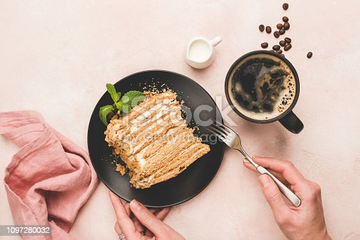 Eating cake with cup of coffee over pink concrete background. Top view. Trendy breakfast or coffee time
