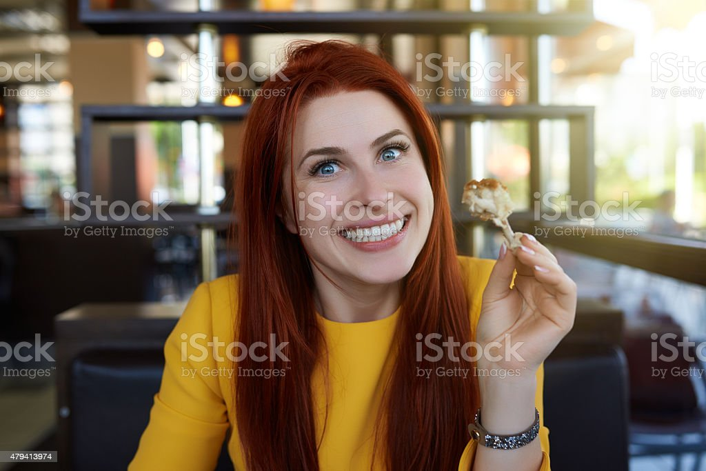 eating chicken drumsticks and smiling stock photo