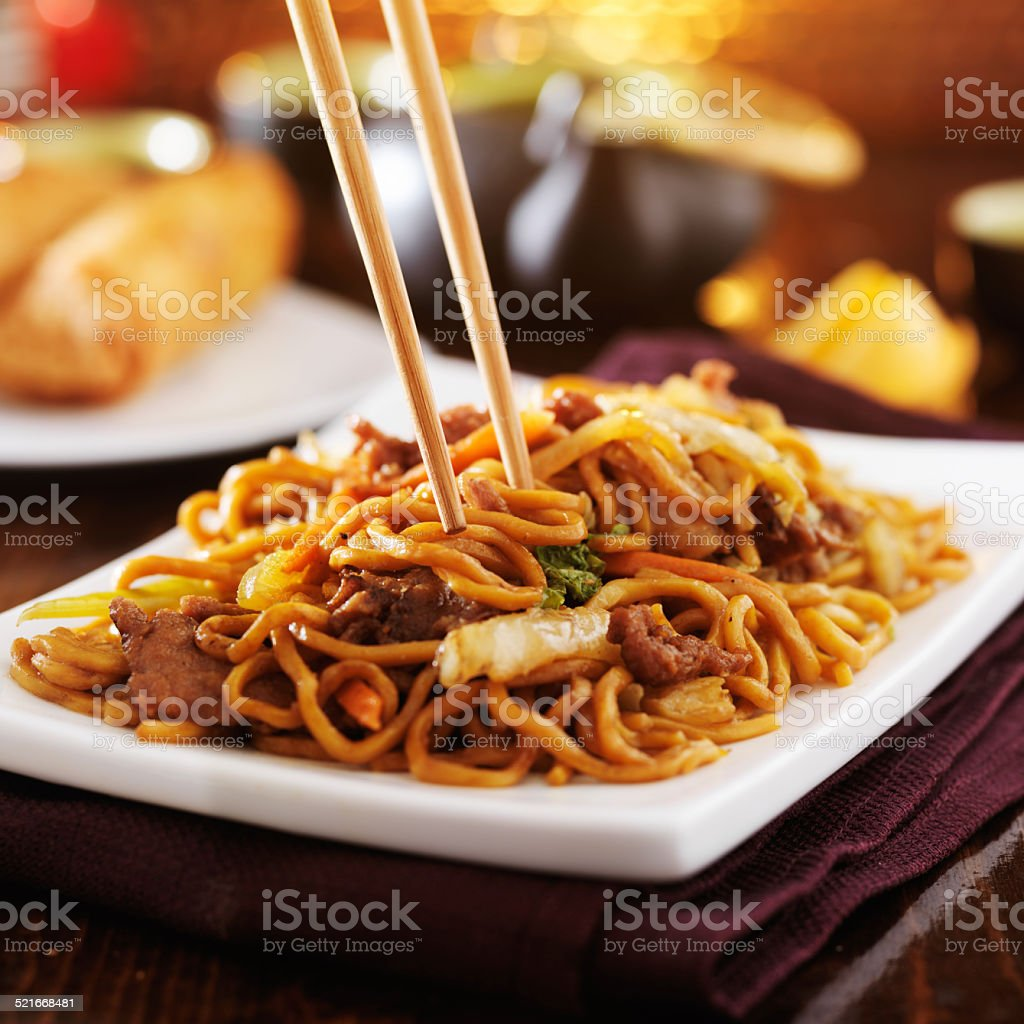 eating chinese beef lo mein with chopsticks stock photo