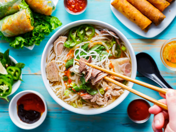 eating colorful vietnamese pho bo with chopsticks - pho soup stock photos and pictures