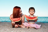 mother with her baby girl lying down on the beach and eating watermelon in summer day.
