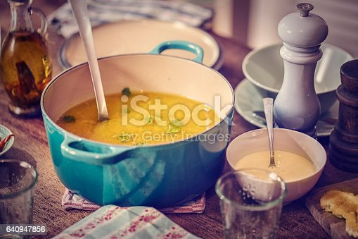 Little girl eating delicious chicken soup with carrots, onions and parsnips. The soup is served in a bowl with creme fresh and grilled toast.