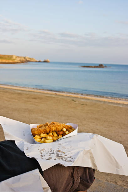 eating fish and chips on the beach - newspaper beach stockfoto's en -beelden