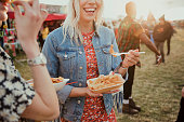 Group of friends eating food at a music festival.