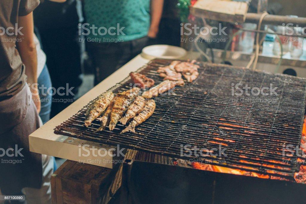 Eating grilled Sardinas on the street at the celebration of Santos Popolares in Lisbon, Portugal stock photo