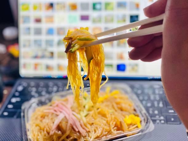 ランチタイムに春麻麺サラダを食べる - WFH / 家にいる ストックフォト