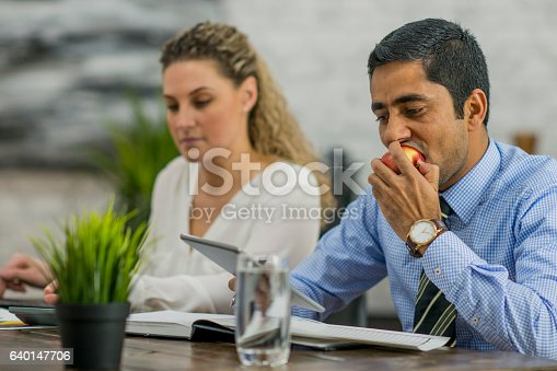 A businessman is eating an apple and drinking water while working with a colleague in the boardroom. He is answering emails on a digital tablet.