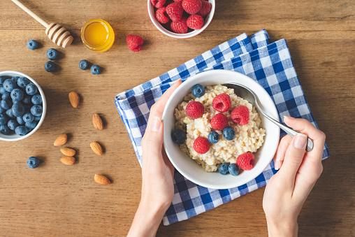 istock Eating healthy breakfast. Oatmeal porridge with berries in hands 1013814260