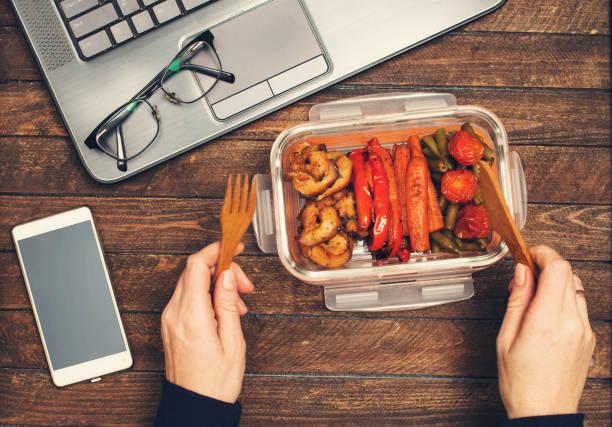 Essen Sie gesund Business Mittagessen am Arbeitsplatz. Gebackenes Gemüse und Hühner-Lunch auf dem Schreibtisch mit Laptop-Smartphone und Brille. – Foto