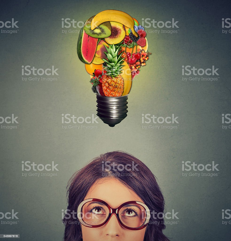 Eating healthy concept. woman looking at fruit light bulb stock photo