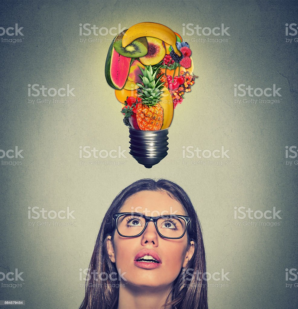 Eating healthy. Woman looking up at fruits light bulb stock photo
