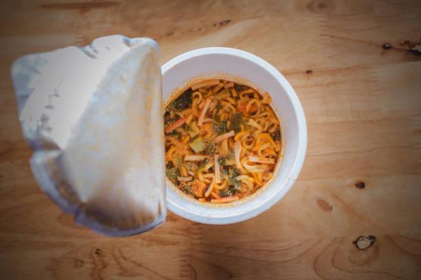 eating instant noodles with a plastic fork - schnelle suppen stock-fotos und bilder