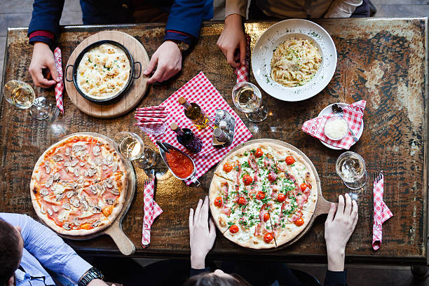 eating italian food in restaurant - pizzeria stock photos and pictures