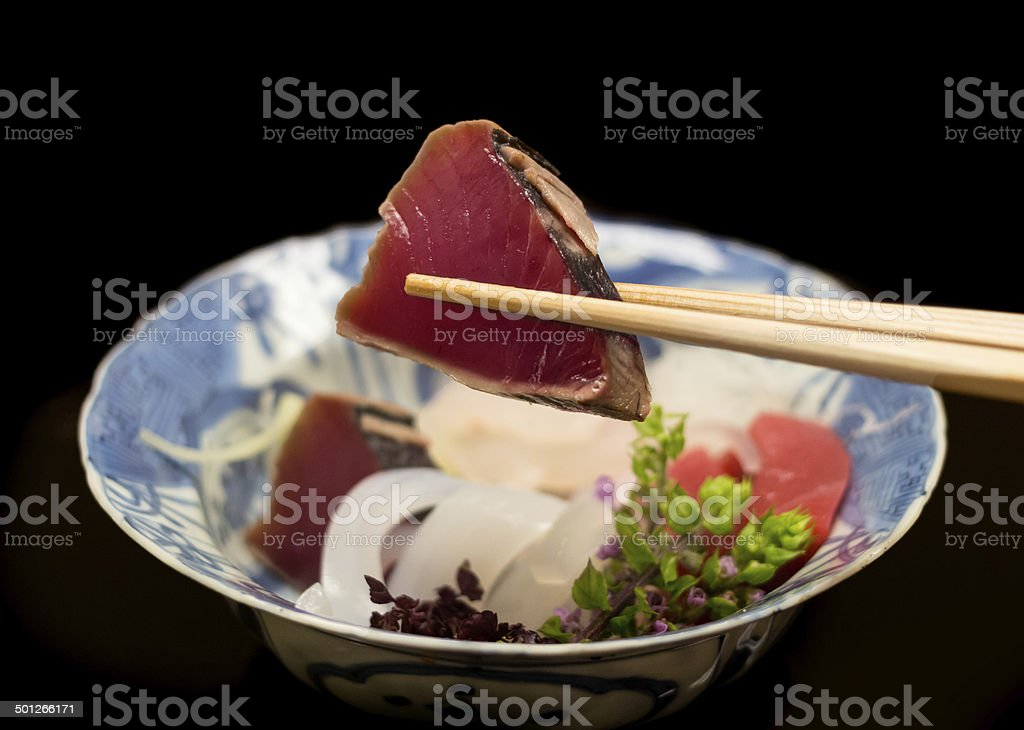 Eating Japense food katsuo no tataki sashimi with chopsticks. stock photo