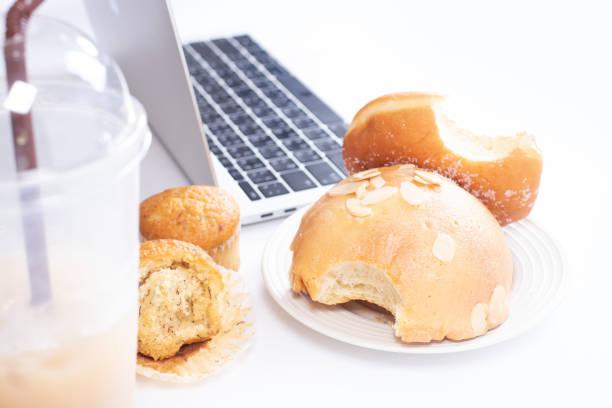 comendo junk food e pão doce na mesa do computador. - junk food - fotografias e filmes do acervo