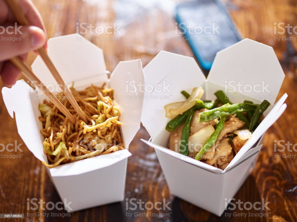 eating lo mein out of chinese take out box - foto de stock