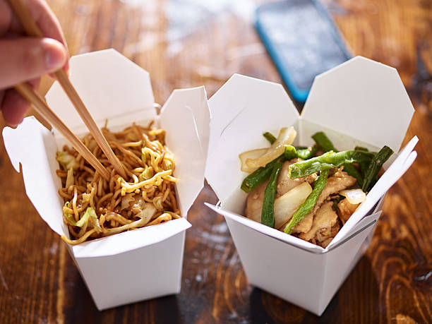 eating lo mein out of chinese take out box stock photo