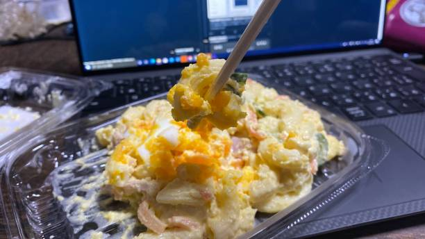 リモート作業中に牧場の時間にキーボードでマカロニサラダを食べる ストックフォト