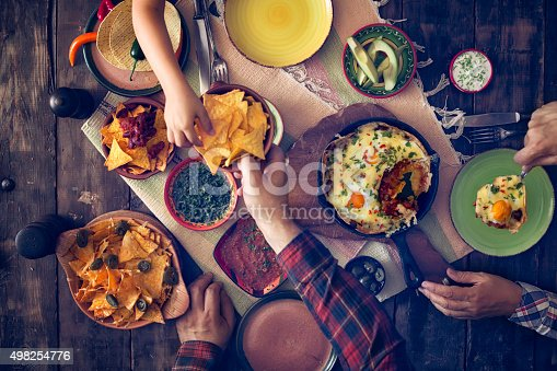 Eating delicious mexican eggs and tortilla chips with salsa and jalapenos. Tortilla chips is a snack made from corn, which are cut into wedges and then baked.