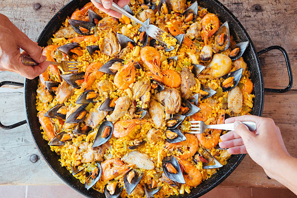 eating mixed paella - paella stock photos and pictures