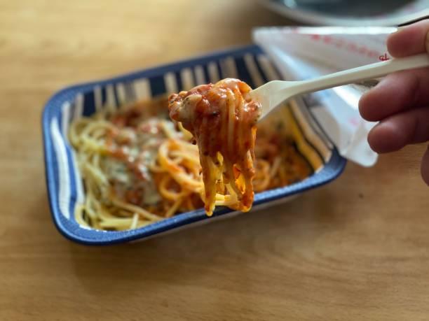 昼食時にパスタ(ミートソース - 冷凍ミール)を食べる ストックフォト