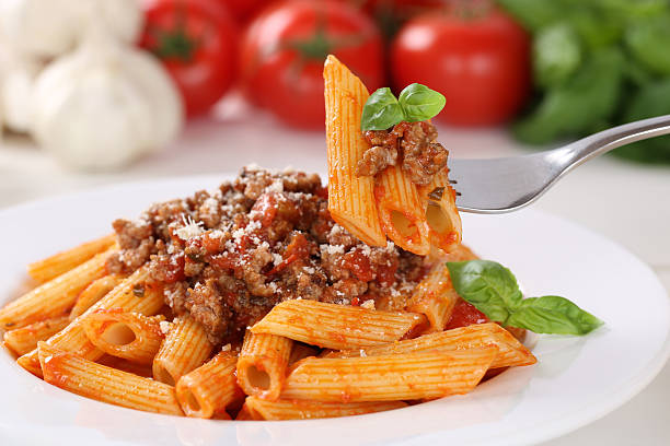 Eating pasta Bolognese or Bolognaise sauce noodles meal Eating pasta Bolognese or Bolognaise sauce noodles meal on a plate rigatoni stock pictures, royalty-free photos & images
