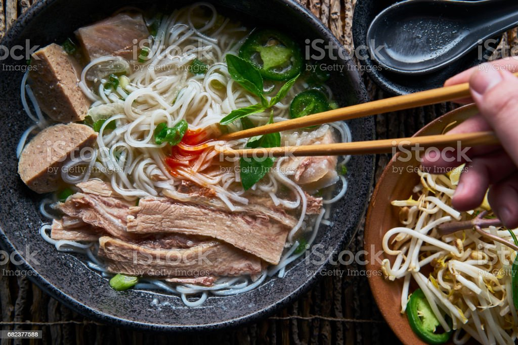 eating pho with brisket and sriracha sauce from overhead view royalty-free stock photo