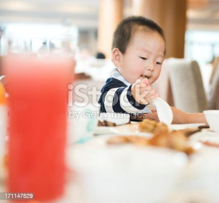 baby boy eating  at a buffet style restaurant.