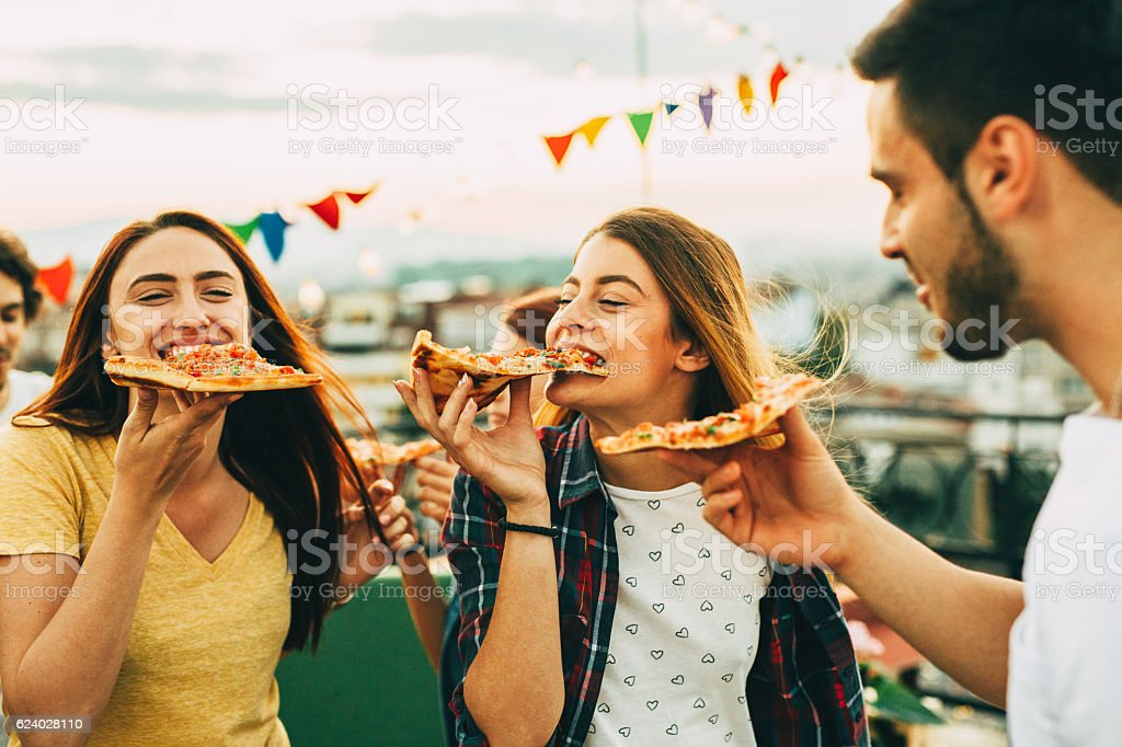 Eating pizza at a party on the roof - foto de acervo