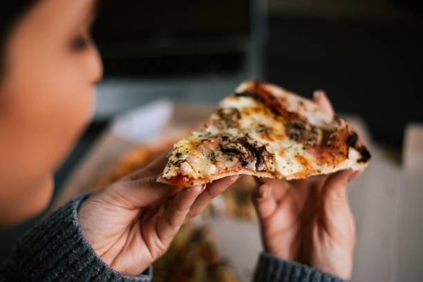 Eating pizza at night. Close-up Eating pizza at night. Close-up unhealthy eating stock pictures, royalty-free photos & images