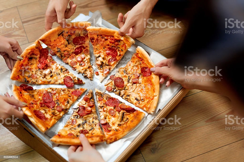 Eating Pizza. Group Of Friends Sharing Pizza. Fast Food, Leisure stock photo