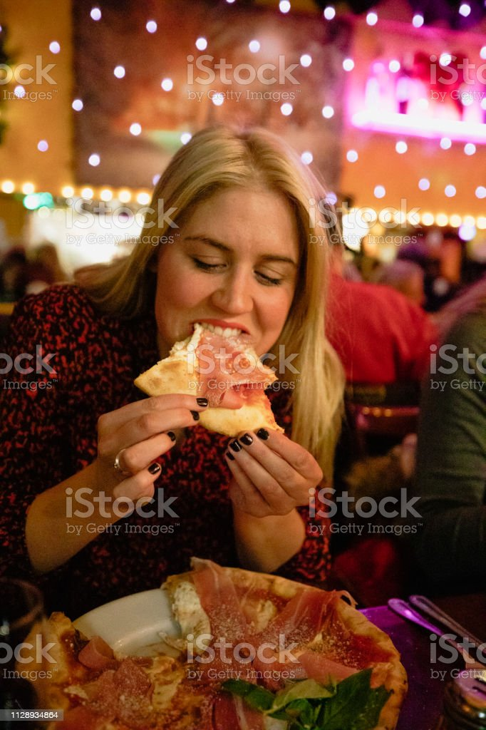 A woman eating pizza in a restaurant surrounded by string lights in...