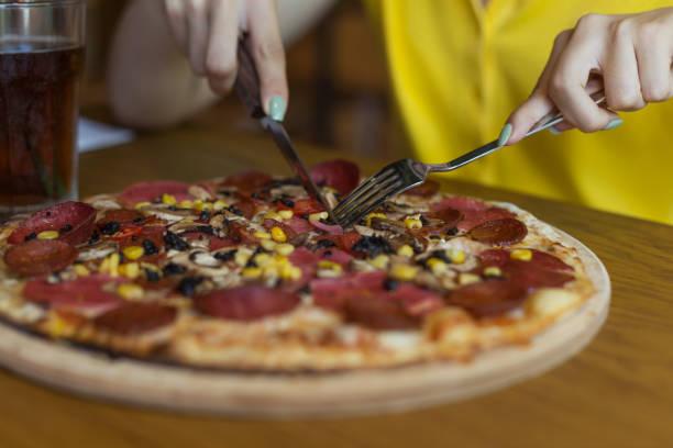 äter pizza på bord - bordsskick bildbanksfoton och bilder