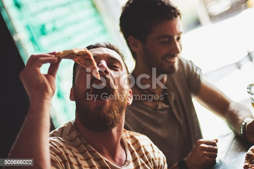 Man eating pizza with his friends in a restaurant