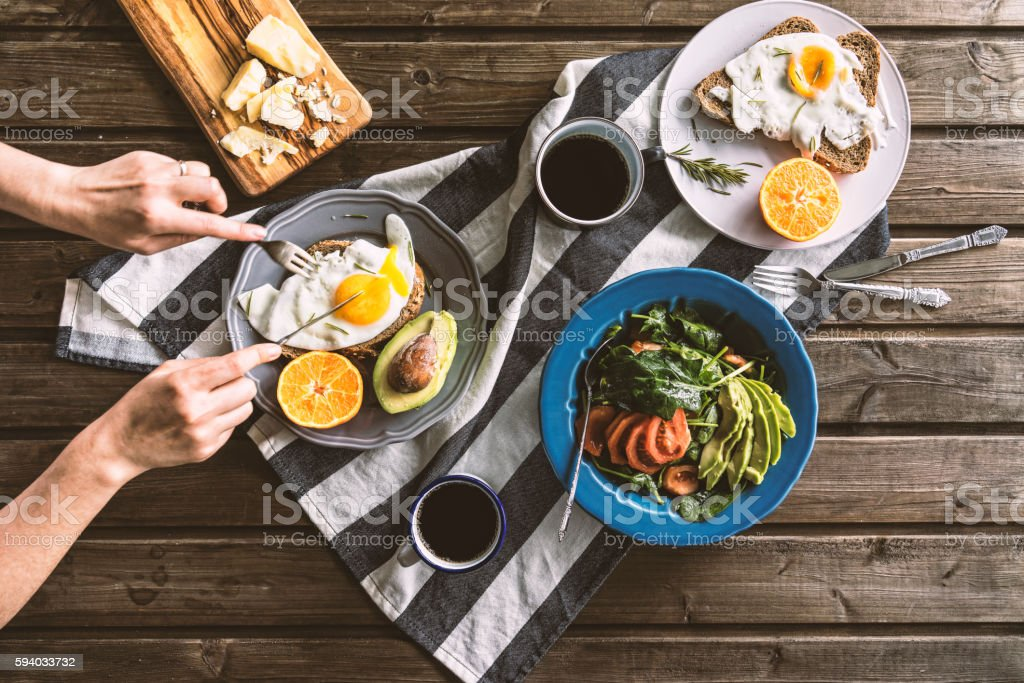 Eating poached eggs for breakfast stock photo