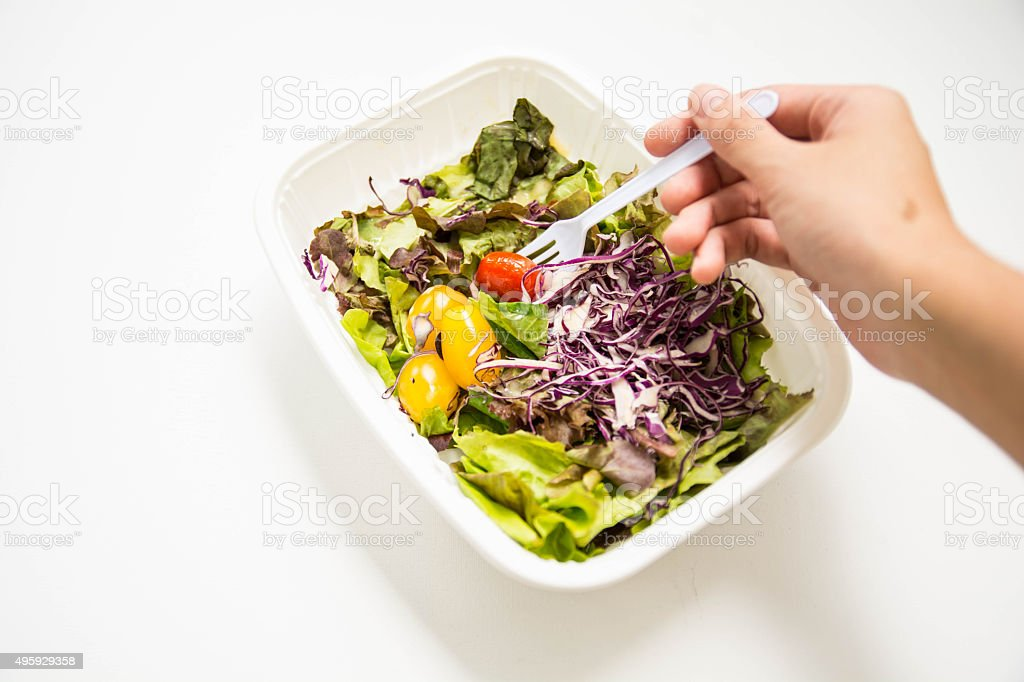 Eating salad in white plastic plate isolated stock photo