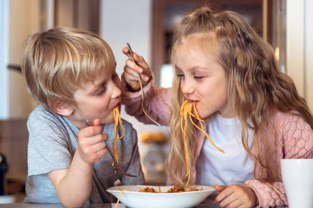 Eating spaghetti with bolognese sauce Cute children having fun while eating spaghetti with bolognese sauce at home bolognese sauce stock pictures, royalty-free photos & images