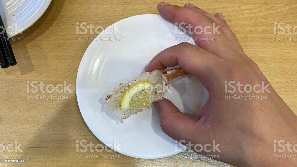 寿司ゴーラウンドレストランで寿司を食べる - 1人のロイヤリティフリーストックフォト