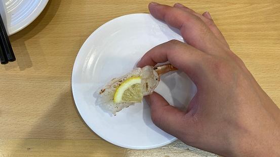 寿司ゴーラウンドレストランで寿司を食べる - 1人のストックフォトや画像を多数ご用意