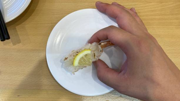 寿司ゴーラウンドレストランで寿司を食べる ストックフォト