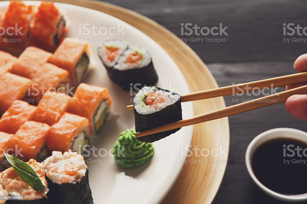 Eating sushi rolls at japanese food restaurant stock photo
