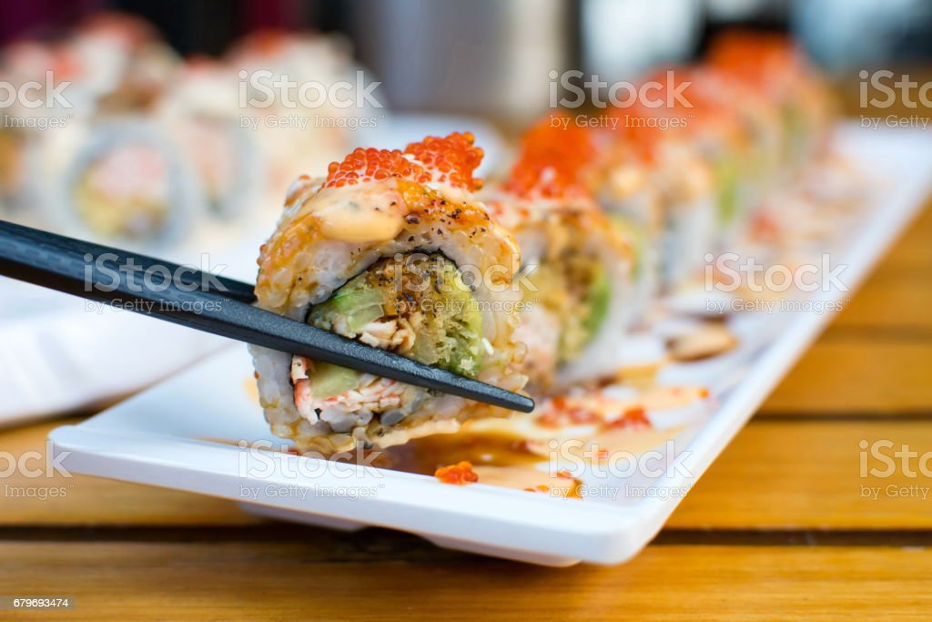Eating sushi rolls with chopsticks stock photo
